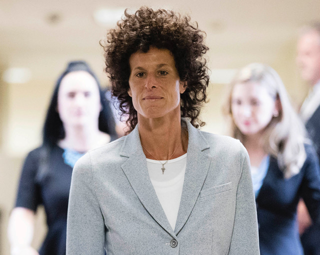 Andrea Constand walking in courthouse to testify, light blue coat