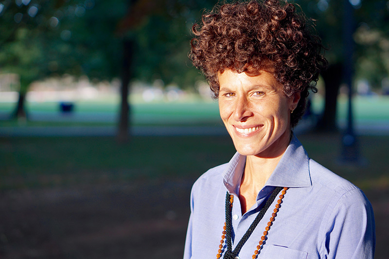 Andrea Constand standing in park, blue shirt, grass in background, wearing necklaces